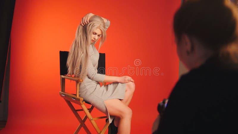Blondy żeński pozować dla fotografa - fasonuje zakulisowego zdjęcie stock