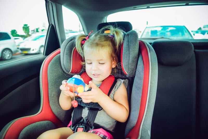 Blondy behandla som ett barn flickan som är fäst med säkerhetsbältet i säkerhetsbilsäte och plaing med leksaken automatiskn behan royaltyfri foto