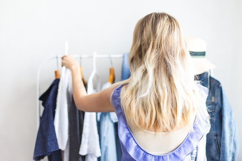 Blondy dziewczyna blisko garderoby z ubraniami no może wybierać co być ubranym obraz royalty free