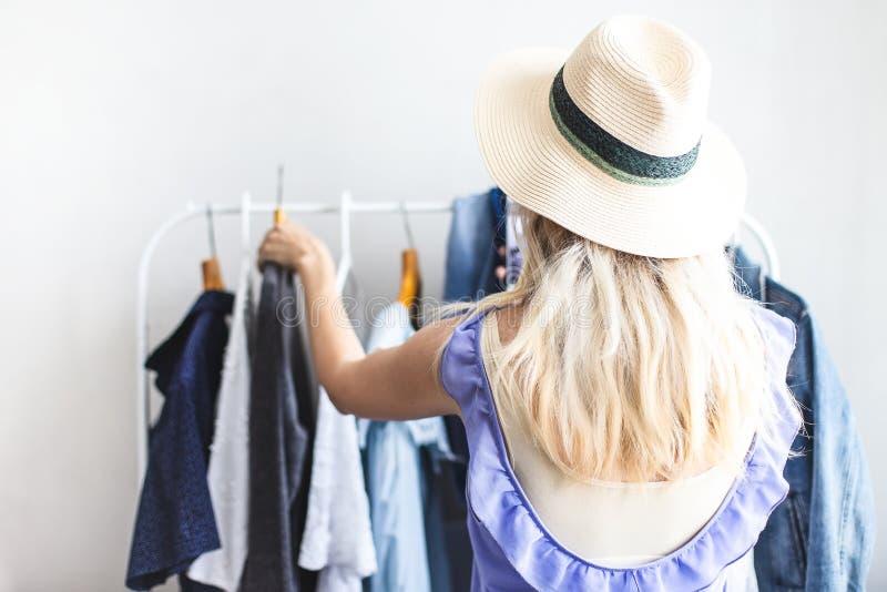 Blondy dziewczyna blisko garderoby z ubraniami no może wybierać co być ubranym zdjęcia stock