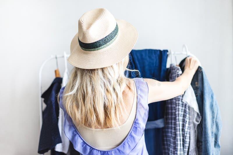 Blondy dziewczyna blisko garderoby z ubraniami no może wybierać co być ubranym zdjęcie royalty free