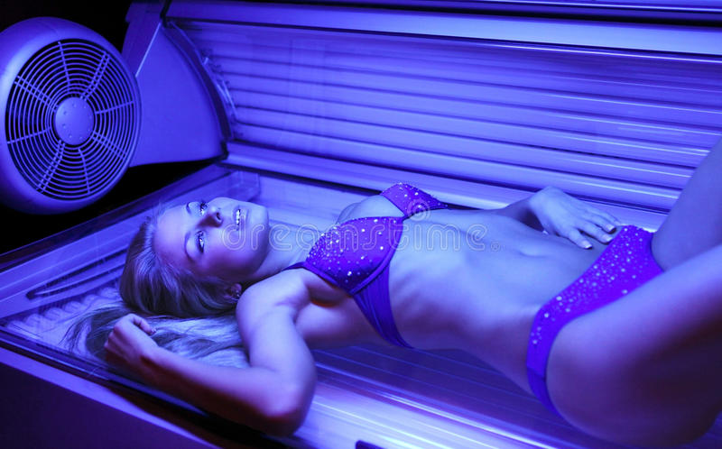 Blondy en solarium imagen de archivo