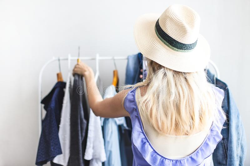 Blondy-Mädchen nahe einer Garderobe mit Kleidung kann was nicht wählen zu tragen stockfotos