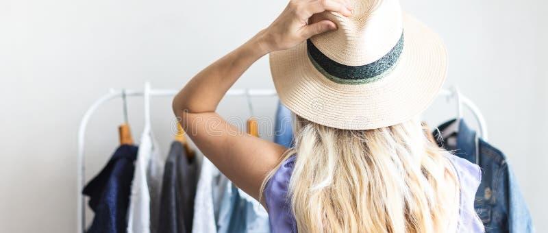 Blondy-Mädchen nahe einer Garderobe mit Kleidung kann was nicht wählen zu tragen lizenzfreie stockfotografie
