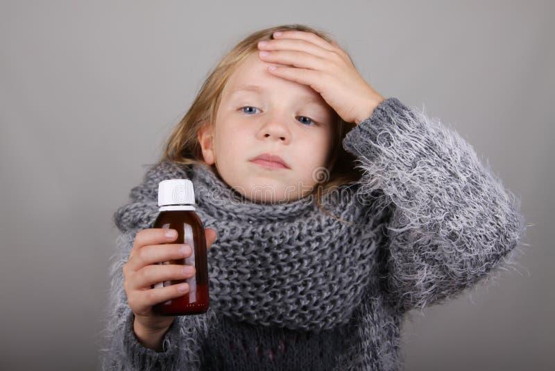 Blondyn małej dziewczynki mienia kasłania syrop w ręce dziecko jest chore Dziecko zimy opieki zdrowotnej grypowy pojęcie fotografia stock