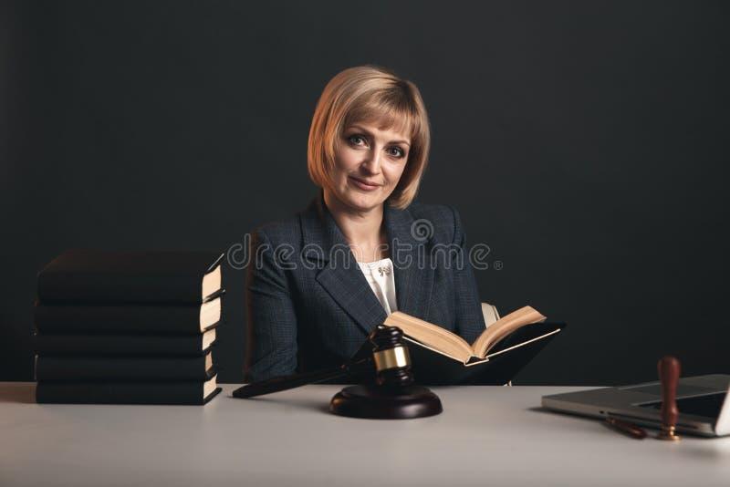 Blondynka żeński adwokat przy miejsce pracy odizolowywającą w pracownianej czytelniczej książce zdjęcia stock