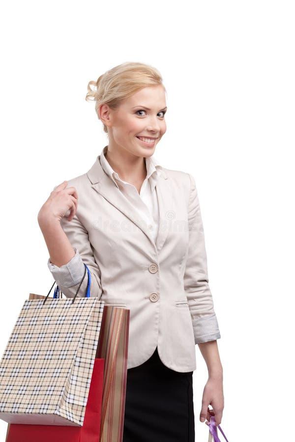 Blondynka atrakcyjny bizneswoman w kostiumu mienia lekkich beżowych torba na zakupy obraz royalty free