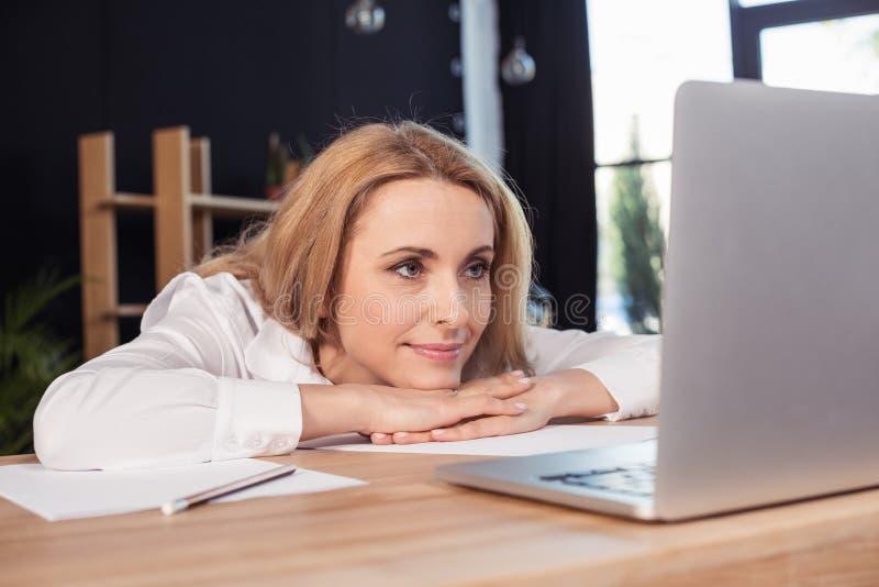 Blondynka bizneswoman patrzeje laptop podczas gdy siedzący przy drewnianym stołem obrazy royalty free