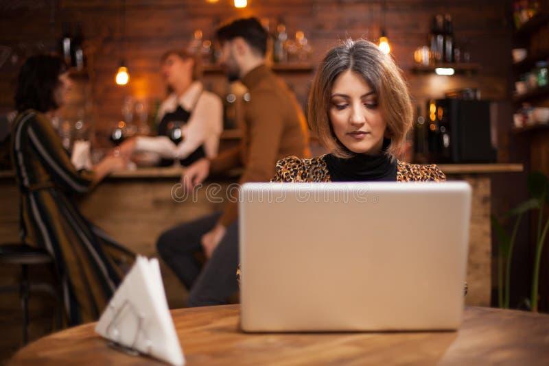 Blondynka bizneswoman pracuje na jej laptopie w sklepie z kawą obrazy royalty free
