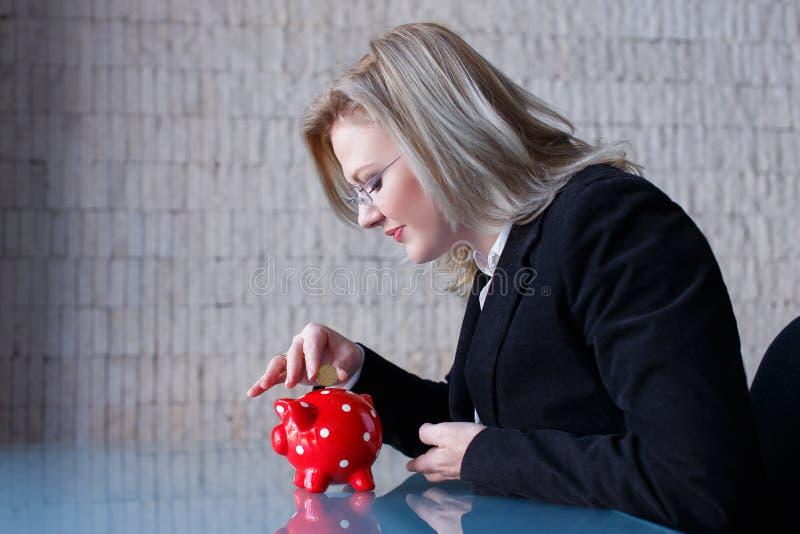 Blondynka bizneswoman stawia monety w prosiątko banka obrazy stock