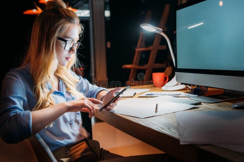 Blondynka caucasian bizneswoman w eyeglasses i obsiadanie używać smartphone przy miejscem pracy z komputerem zdjęcia royalty free