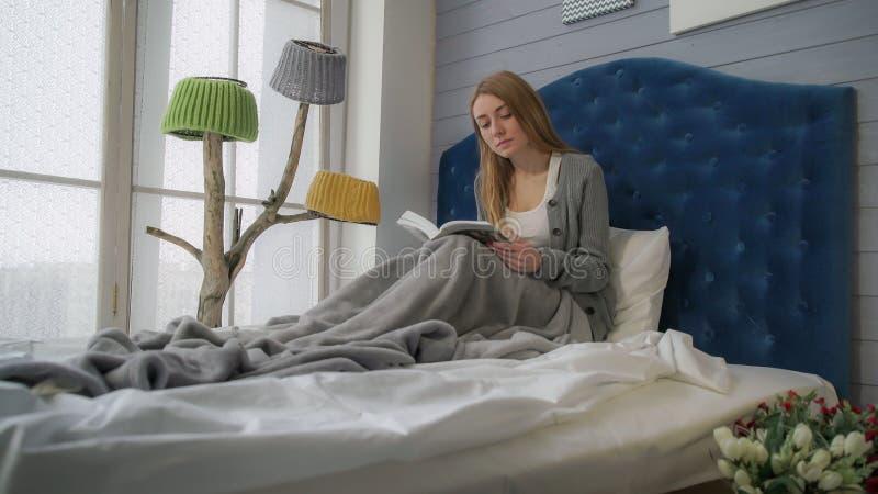 Blondynka czyta książkę podczas gdy siedzący w łóżku zdjęcie stock