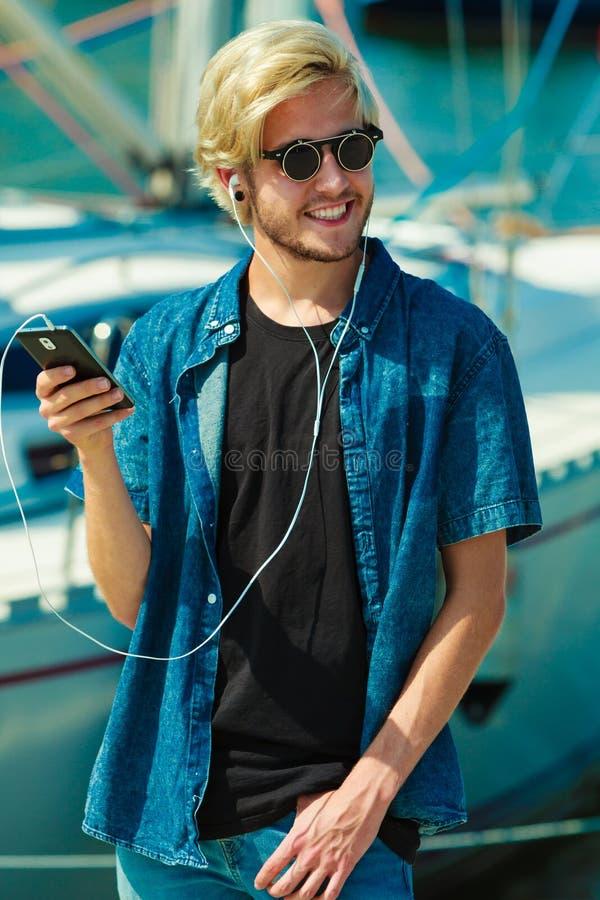 Blondynka mężczyzna słucha muzyka w okularach przeciwsłonecznych obrazy stock