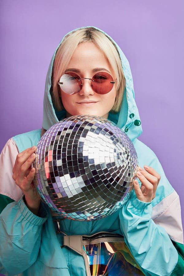 Blondynka modnisia kobieta pozuje z olśniewającym discoball nad fiołkowym tłem zdjęcia stock