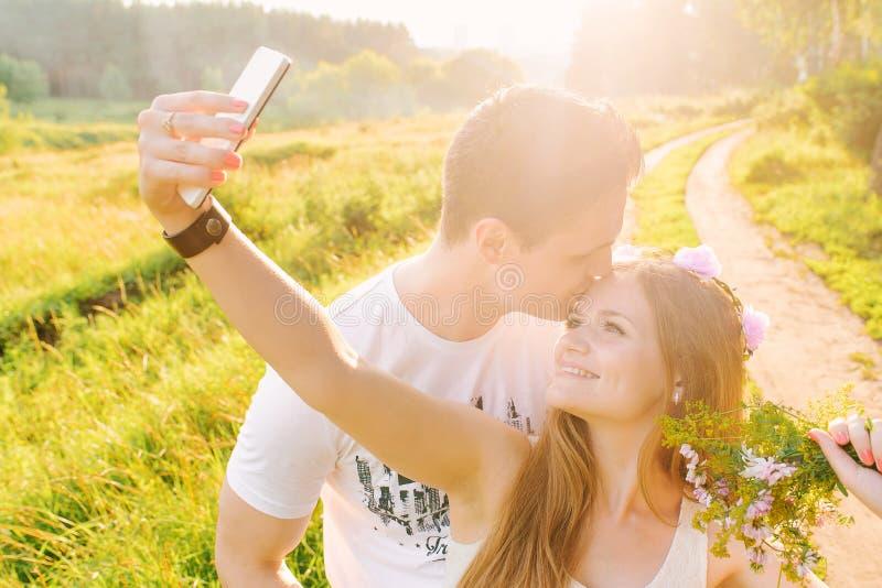 Blondynka robi selfie z jej mężczyzna całowaniem fotografia stock