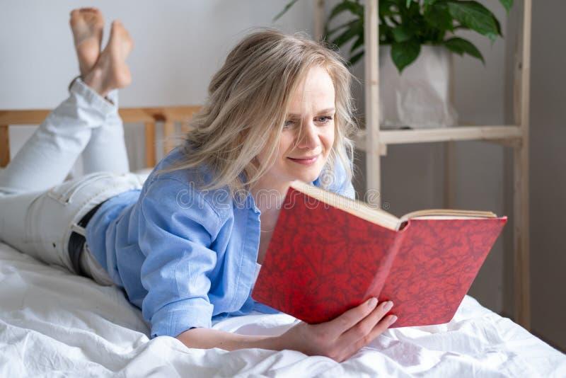 Blondynka trzymająca otwartą książkę i czytająca leżącą na łóżku Wypoczynek, pobyt w domu i kwarantanna Czas na siebie fotografia royalty free