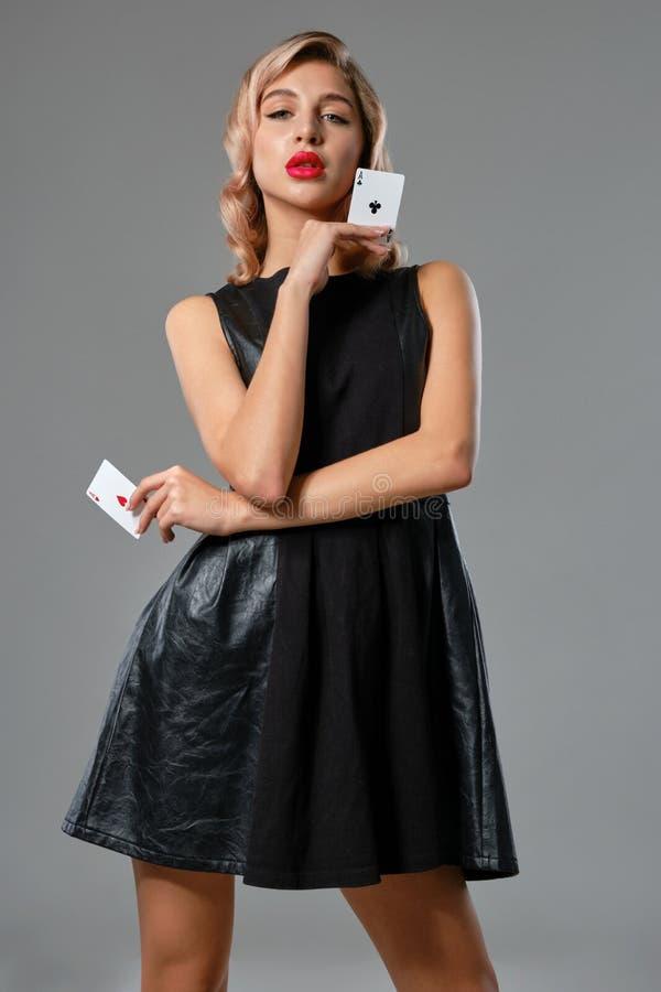 Blondynka w czarnej stylowej sukience pokazuje dwie karty do gry, pozując się na szarym tle Rozrywka hazardowa obraz stock