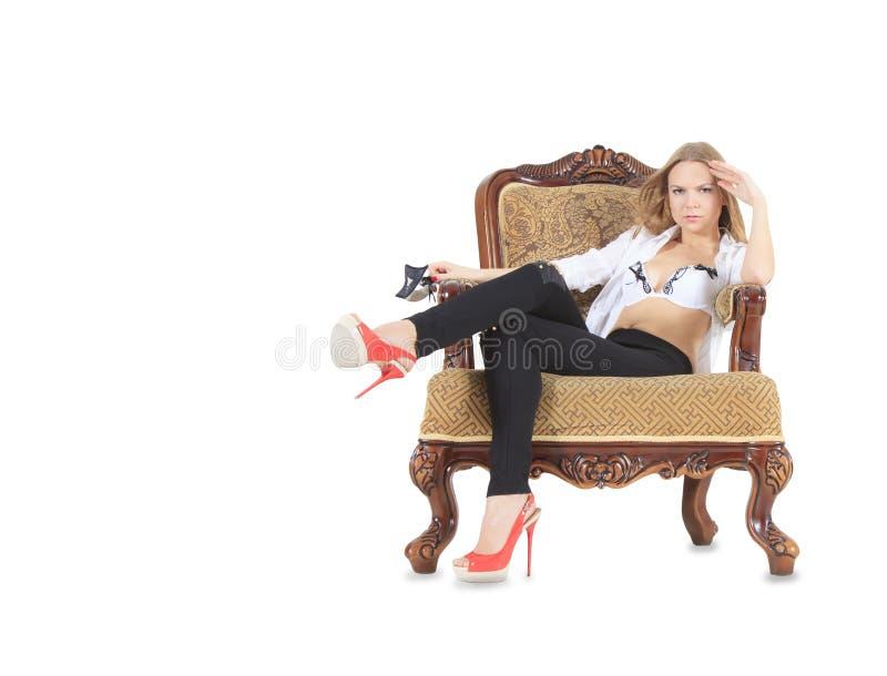 Blondynka w czerwieni kuje obsiadanie w tronie zdjęcia stock