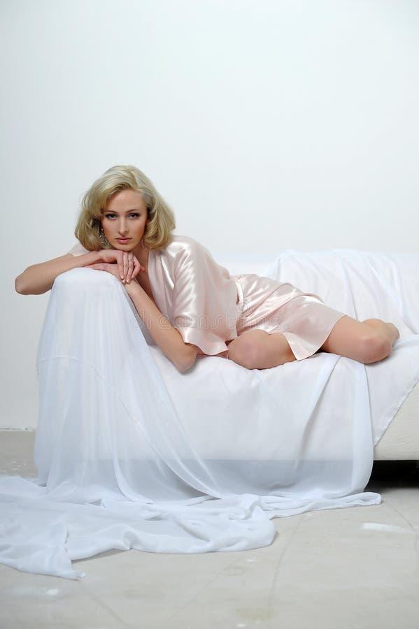 blondynka w jedwabniczej opatrunkowej todze na kanapie obraz stock