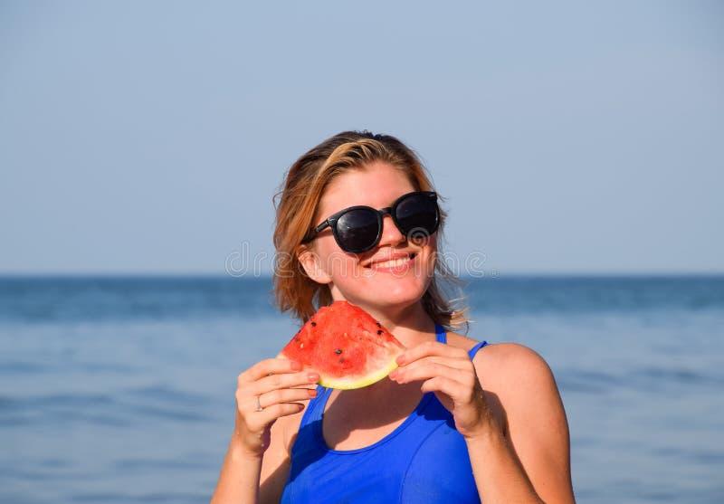 Blondynka w okularach przeciwsłonecznych je arbuza morzem Soczysty arbuz w rękach kobieta fotografia stock