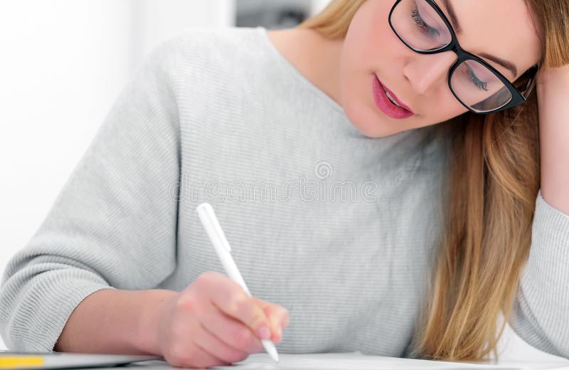 Blondynka w szkłach pracuje z papierami obok laptopu przy jej biurkiem Młoda kobieta w biurze lub studiowaniu zdjęcia stock