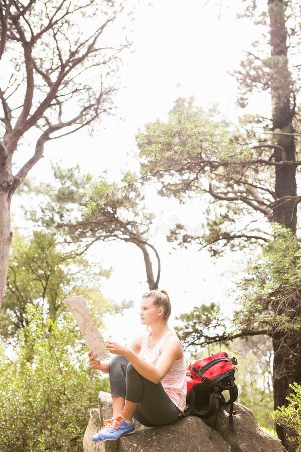 Blondynka wycieczkowicza obsiadanie na skały i czytania mapie zdjęcia royalty free