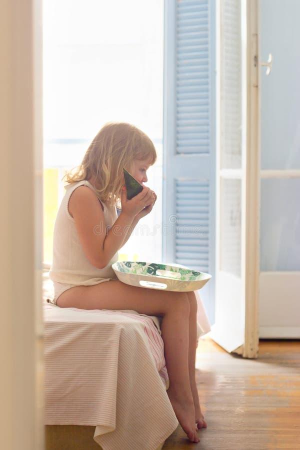 Blondynka zjada arbuz na łóżku, latem rano obraz stock