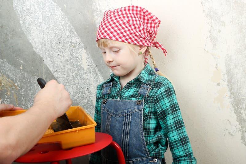 Blondynki błękitnooka mała dziewczynka robi naprawom z ojcem w mieszkaniu fotografia royalty free