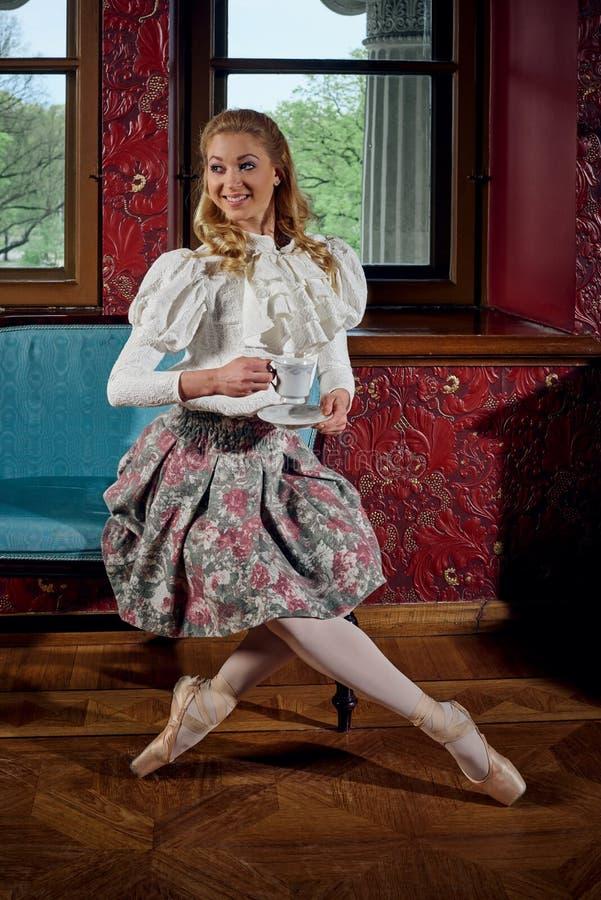 Blondynki balerina w mody odzieżowym obsiadaniu na kanapie i pić herbaty obraz royalty free