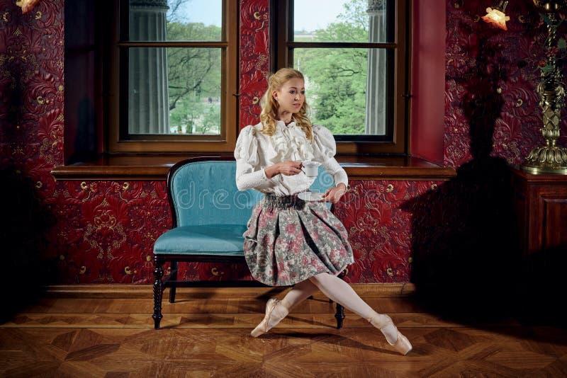 Blondynki balerina w mody odzieżowym obsiadaniu na kanapie i pić herbaty fotografia royalty free
