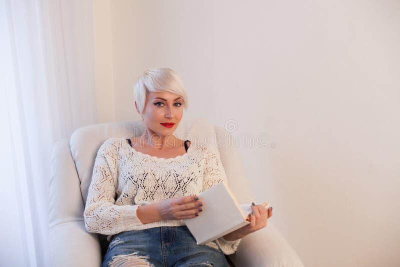 Blondynki dziewczyna czyta książkowego wiedzy szkolenie obraz stock