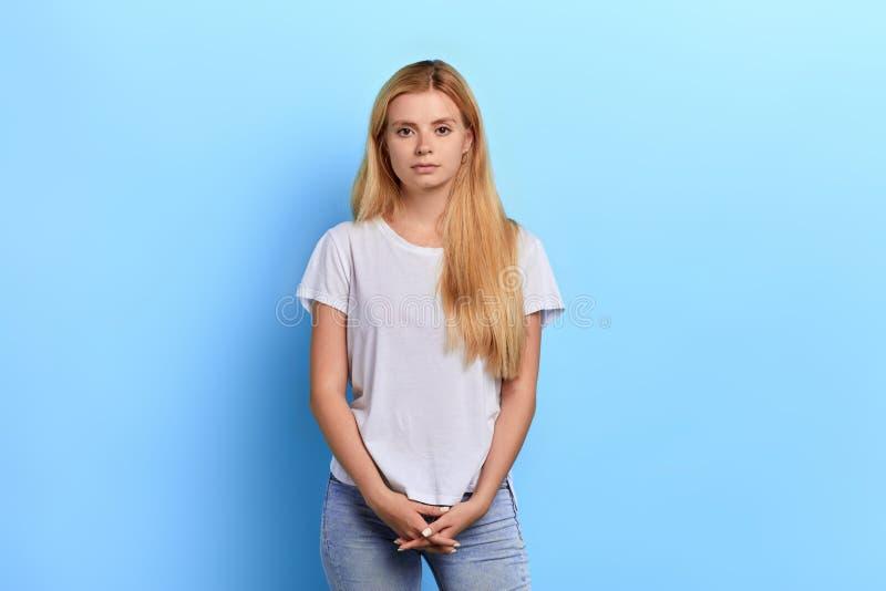 Blondynki dziewczyna jest ubranym białą koszulkę, cajgi pozuje kamery błękita ściana obraz royalty free