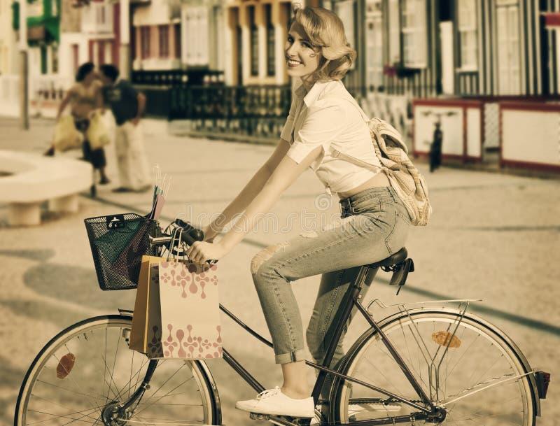 Blondynki dziewczyna na bicyklu w zakupy czasie zdjęcia royalty free