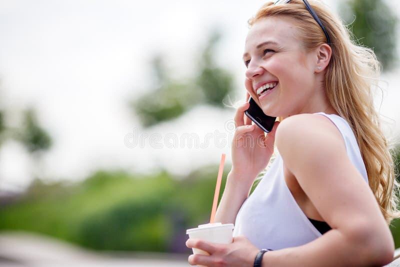 Blondynki dziewczyna opowiada na telefonie w parkowej ławce z kawą obraz stock
