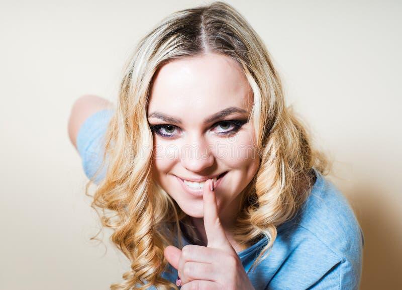Blondynki dziewczyna pokazuje gest zaciszność obraz stock