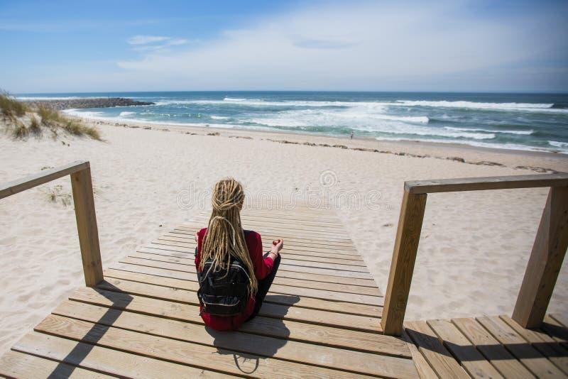 Blondynki dziewczyna siedzi na ścieżce ocean zdjęcia royalty free