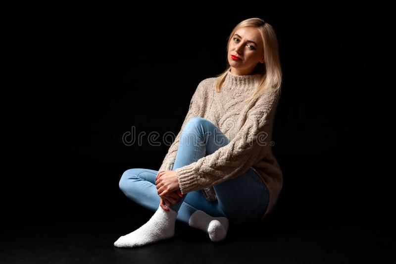 Blondynki dziewczyna siedzi na podłodze w studiu na czarnym tle w cajgach, pulower i skarpety, ona nogi krzyżują, ona patrzeją obrazy stock