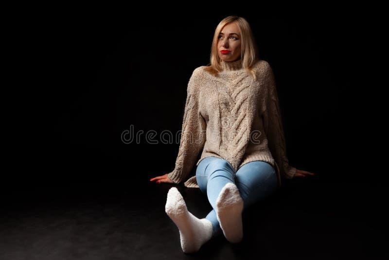 Blondynki dziewczyna siedzi na podłodze w studiu na czarnym tle w cajgach, pulower i skarpety, ona nogi rozciągają i fotografia royalty free