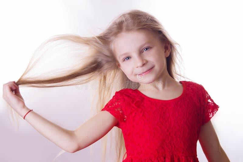Blondynki dziewczyna w czerwieni sukni z falowaniem wiatrowym włosy obraz stock