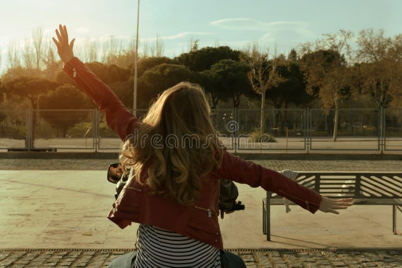 Blondynki dziewczyna w czerwonej skórzanej kurtce z rękami szeroko rozpościerać obraz royalty free