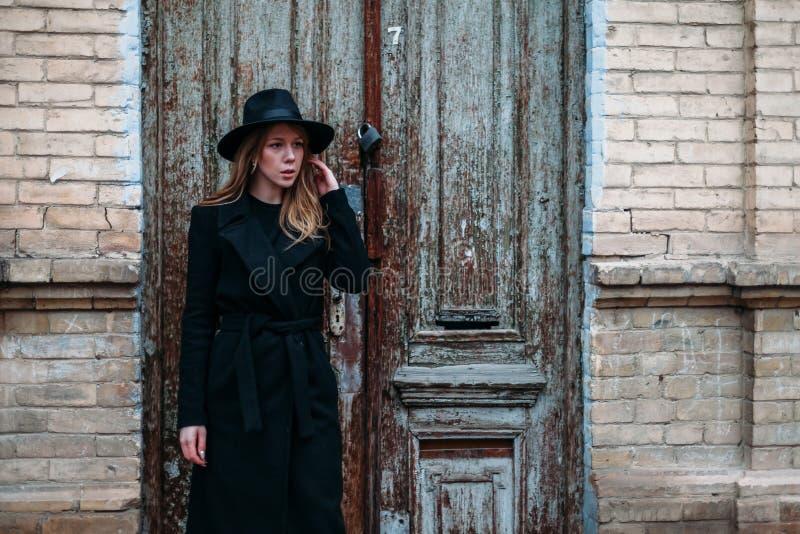 Blondynki dziewczyna z długie włosy, w czarnym żakiecie w kapeluszu, stojaki na tle rocznik cegły antykwarski stary drewniany drz obraz stock