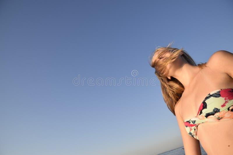 Blondynki dziewczyna z jej włosy na niebieskiego nieba tle Piękna młoda kobieta w kolorowym bikini zdjęcia royalty free