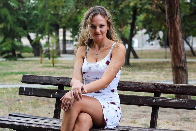 Blondynki dziewczyna Z Kędzierzawego włosy obsiadaniem na ławce w parku Z fotografia stock