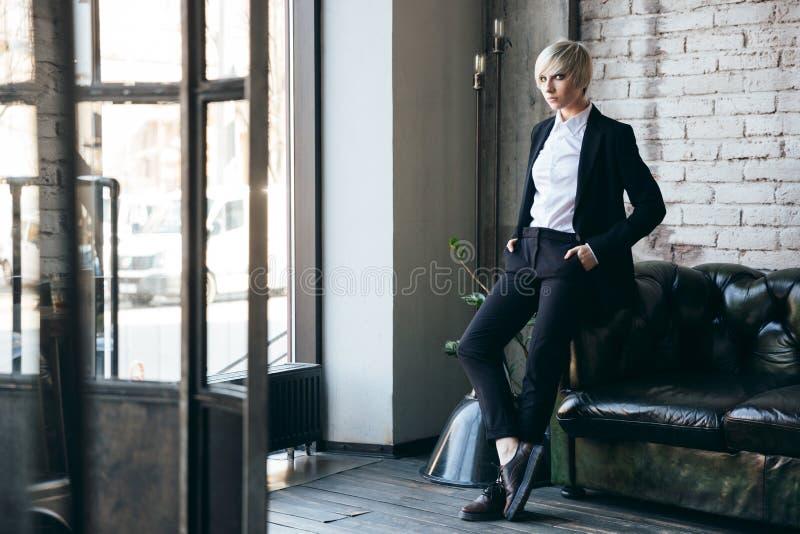 Blondynki dziewczyny śliczna pozycja blisko leżanki w kawiarni zdjęcie royalty free