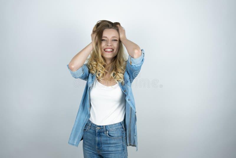 Blondynki dziewczyny mienia ręk blisko głowa patrzeje zdziwionego białego odosobnionego tło fotografia royalty free