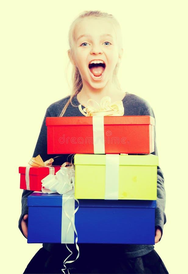 blondynki dziewczyny mienie w ręka udziałach pudełka z prezentami na odosobnionym tle fotografia royalty free