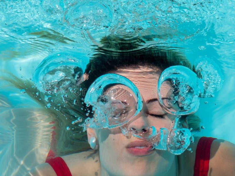Blondynki dziewczyny pikowanie w basenie i oddychanie za powietrzu robić bąblowi obraz stock
