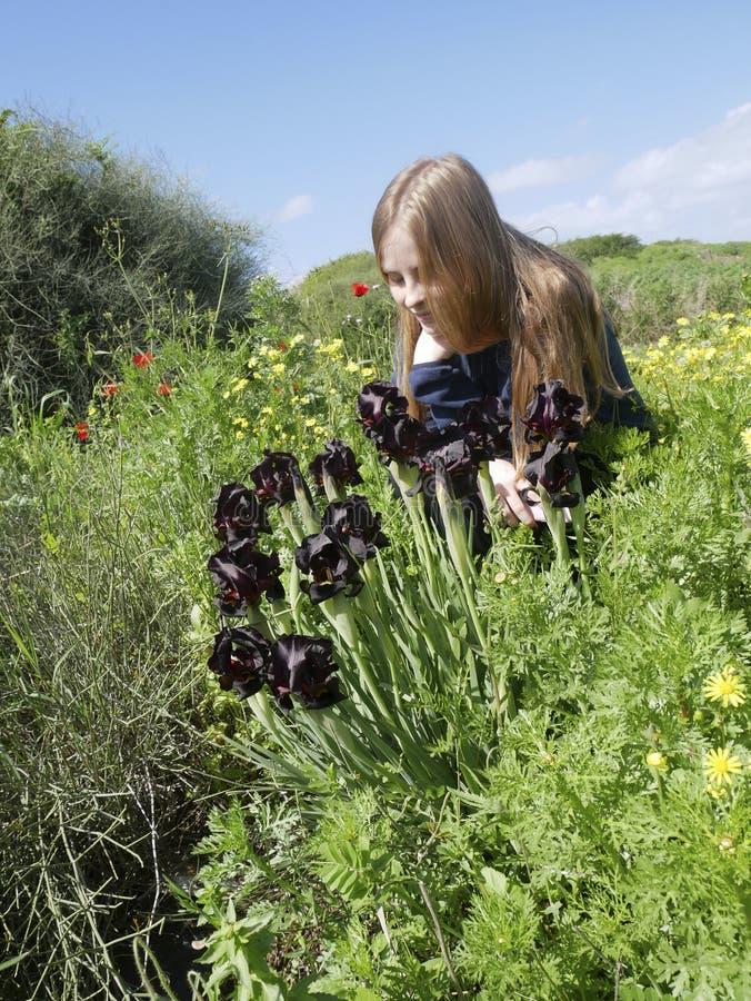 Blondynki dziewczyny spojrzenia przy kwiatami Irysowymi w ochraniającym naturalnym terenie fotografia stock