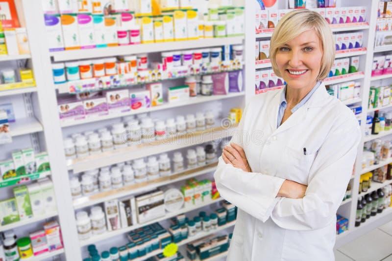 Blondynki farmaceuta z rękami krzyżował uśmiecha się przy kamerą zdjęcie royalty free