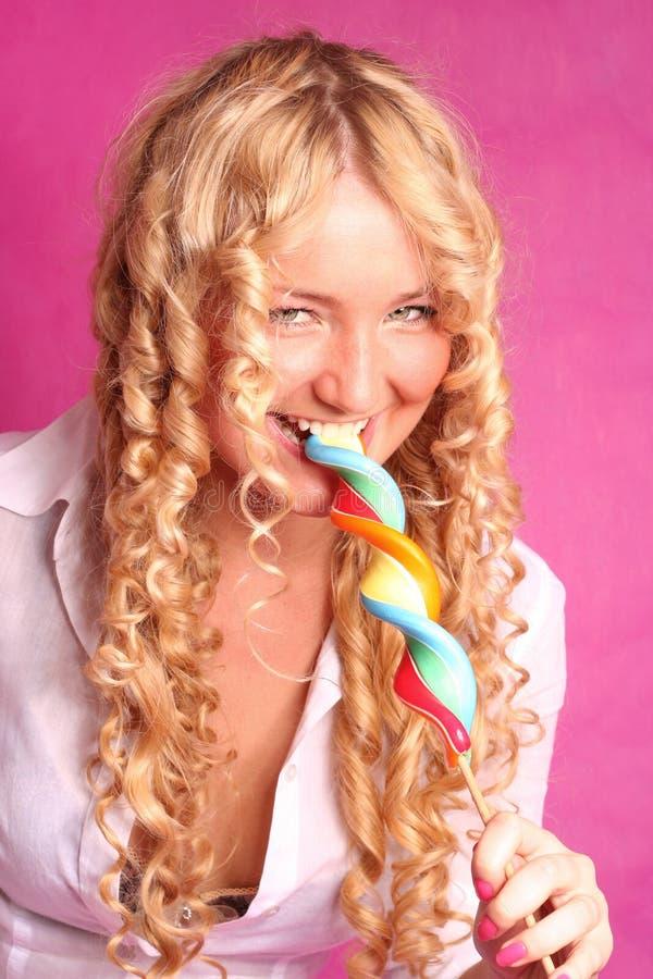 Blondynki kędzierzawej dziewczyny zjadliwy lizak zdjęcie royalty free